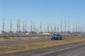 FILE - In this Wednesday, Feb. 25, 2015, file photo, more than 30 oil drilling rigs are idle in a Helmerich & Payne, Inc. yard in Odessa, Texas, along Highway 80, as rig counts drop in the Permian Basin. The price of oil continues to fall, extending a slide that has already gone further and lasted longer than most thought, and probing depths not seen since 2003. Lower crude prices are leading to lower prices for gasoline, diesel, jet fuel and heating oil, giving drivers, shippers, and many businesses a big break on fuel costs. But layoffs across the oil industry are mounting, and bankruptcies among oil companies are expected to soar. (Courtney Sacco/Odessa American via AP) MANDATORY CREDIT