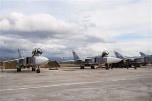 A line-up of Russian bombers stand on tarmac as another plane takes off in the background at Hemeimeem air base in Syria on Wednesday Jan. 20 2016. Russian warplanes have flown over 5,700 combat missions since Moscow launched its air campaign in Syria on Sept. 30 2015. (AP Photo/Vladimir Isachenkov)