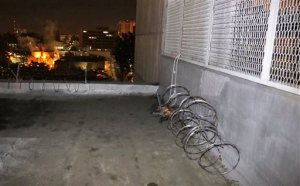 This Jan. 23, 2016 photo provided by the Orange County Sheriff's Office shows the exterior of Central Men's Jail in Santa Ana, Calif., showing where razor wire was removed from a parapet, center rear, and a rope-like line, seen at right, which authorities believe three inmates used to repel to the ground during their escape sometime Friday, Jan. 22. (Orange County Sheriff's Office via AP)