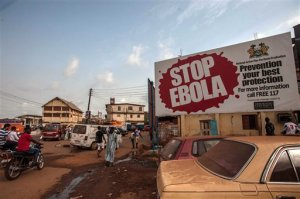 People pass a banner reading 'STOP EBOLA'  forming part of Sierra Leone's Ebola free campaign in the city of  Freetown, Sierra Leone, Friday, Jan. 15, 2016. A corpse has tested positive for Ebola in Sierra Leone, an official said Friday, the day after the World Health Organization declared the outbreak over in West Africa.  (AP Photo/Aurelie Marrier d'Unienville)