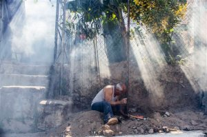 A man works on a fence amidst a cloud of insecticide as city workers fumigate to combat the Aedes Aegypti mosquitoes that transmits the Zika virus, at the San Judas Community in San Salvador, El Salvador, Tuesday, Jan. 26, 2016.  Worries about the rapid spread of Zika through the hemisphere has prompted officials in El Salvador, Colombia and Brazil to suggest women stop getting pregnant until the crisis has passed. (AP Photo/Salvador Melendez)