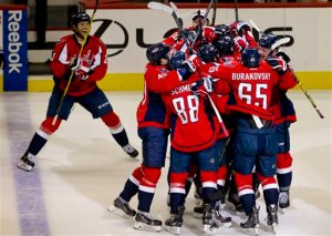The Washington Capitals swarm the ice around left wing Alex Ovechkin, of Russia, in celebration after Ovechkin scored his 500th career NHL goal during the second period of a hockey game against the Ottawa Senators in Washington, D.C., Sunday, Jan. 10, 2016. (AP Photo/Jacquelyn Martin)