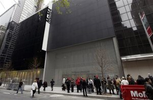 FILE - In this Nov. 20, 2004, file photo, people pass in front of the Museum of Modern Art in New York. The museum's revised expansion plan was made public, Wednesday, Jan. 27, 2016. The work will add about 50,000 square feet of exhibition space, enhance galleries and replace a 1939 staircase that was removed. The museum will remain open throughout the construction as the three-phase, $400 million project, is expected to be completed in 2019 or 2020. (AP Photo/Gregory Bull, File)
