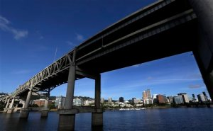 FILE - In this Aug. 4, 2015, file photo, downtown Portland, Ore., is visible under the Interstate-5 Marquam Bridge on the Willamette River. There are numerous bridges in Portland spanning the river, varying in age and ability to withstand a major earthquake. For the past few years emergency officials in the Pacific Northwest have been drafting detailed contingency plans for the day a mega-quake and tsunami hit the region. What planners envision is a massive response that would eclipse the response to any natural disaster so far in U.S. history.  (AP Photo/Don Ryan, File)