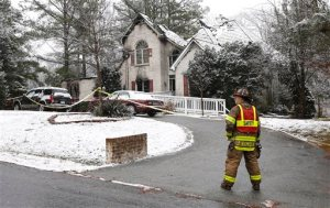 A firefighter stands on the scene where a house fire took place, Sunday, Jan. 17, 2016 in Chesterfield County, Va. Emergency response officials say five people were killed in the early morning fire in suburban Richmond. (Alexa Welch Edlund/Richmond Times-Dispatch via AP)