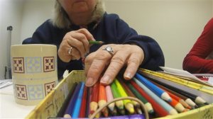 In this Dec. 14, 2015 photo, Mary Federer looks through colored pencils at the DeForest Public Library in DeForest, Wis. Libraries and other groups nationwide are setting up get togethers for adults to color as the practice becomes more and more popular. (AP Photo/Carrie Antlfinger)