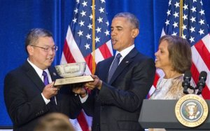 President Barack Obama, center, is presented a commemorative bowl from Rep. Mark Takai, D- Hawaii, left, and Rep. Robin Lynne Kelly, D-N.Y., right, before speaking at the House Democratic Issues Conference in Baltimore, Md., Thursday, Jan. 28, 2016. (AP Photo/Pablo Martinez Monsivais)