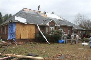 Friends and neighbors work on the roof of the home of Debbie McCormick on Shelby Road near Newton, Miss., that received extensive damage after a storm Tuesday, Feb. 2, 2016. A tornado damaged homes and at least one church, and strong winds damaged student housing at a community college Tuesday in eastern Mississippi. Authorities said no injuries were immediately reported. (Robbie Robertson/The Newton County Appeal via AP)