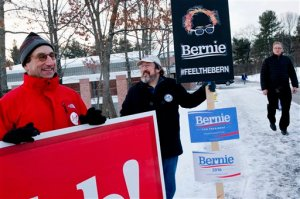 Marc Scheineson of McLean, Va., left, campaigns for Republican presidential candidate, former Florida Gov. Jeb Bush, as Atlant Schmidt of Nashua, N.H., campaigns for Democratic presidential candidate Sen. Bernie Sanders, I-Vt., while a voter walks past at a polling location at Broad Street Elementary in Nashua, N.H., Tuesday, Feb. 9, 2016, during the New Hampshire primary. (AP Photo/Jacquelyn Martin)