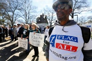 FILE - In this Thursday, Feb. 18, 2016 file photo, Milton Phelps of Jackson, right, stands with Maureen Phillips, center, and her sister Dixie Daniels, both of Gulfport, in calling for a change to the current Mississippi state flag at a rally to remove the Confederate battle emblem from the flag at the state Capitol in Jackson, Miss. Mississippi Gov. Phil Bryant is proclaiming April 2016 as Confederate Heritage Month, but without mentioning slavery. He signed it days before legislators killed bills that would have either removed the Confederate battle emblem from the 122-year-old state flag or stripped state money from colleges and local governments that refuse to fly the current banner. (AP Photo/Rogelio V. Solis, File)