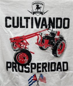 """In this Feb. 12, 2016 photo, a logo on a T-shirt which reads in Spanish """"Cultivating prosperity"""" hangs on display at the office of tractor maker Saul Berenthal in Raleigh, N.C. The Obama administration has approved the first U.S. factory in Cuba in more than half a century, allowing a pair of former software engineers to build a plant assembling as many as 1,000 small tractors a year. The partners were notified by Treasury Department officials last week that it was legal for them to open their Oggun tractor assembly plant in a special economic zone created by the Cuban government to draw foreign investment. (AP Photo/Gerry Broome)"""