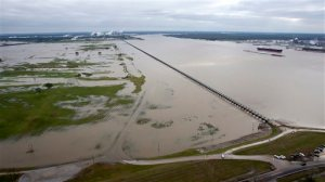 CORRECTS TO REFLECT POOL STATUS OF PHOTO - Workers with the U.S. Army Corps of engineers drain water from the Mississippi River, right, into the Bonnet Carre Spillway Sunday, Jan. 10, 2016, in Norco, La. The Mississippi River water levels are rising because of heavy December rain in the Midwest. The opening of the Bonnet Carre Spillway helps relieve pressure on New Orleans-area levees by making sure the water doesn't flow faster than 1.25 million cubic feet per second through the city.  (Scott Threlkeld/The Advocate via AP, Pool)