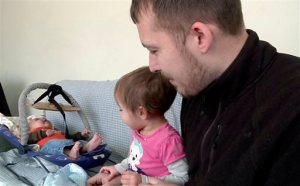 In this Friday, Feb. 5, 2016 image from video, Luke Waid discusses the lead-contamination in Flint's water as he watches his 2-year-old daughter, Sophia, and infant son, Luke Jr, in their Flint, Mich., home. A federal lawsuit filed Monday, Feb. 8, 2016, seeks unspecified damages from Michigan Gov. Rick Snyder, the state of Michigan and city of Flint claiming Sophia has been sickened by the city's water. (AP Photo/Mike Householder)