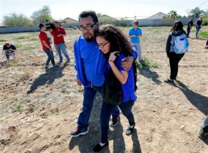 A father and daughter reunite in a vacant field, Friday, Feb. 12, 2016, in Glendale, Ariz., after two students were shot and killed at Independence High School in the Phoenix suburb. The danger at the campus was over, police said, as worried parents crowded stores nearby to meet their children.  (AP Photo/Matt York)