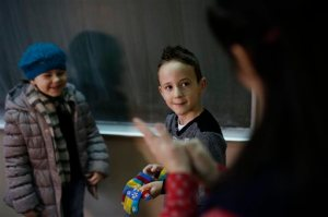 In this photo taken Thursday, Feb. 4, 2016, Bosnian boy Zejd Coralic, center, learns sign language from teacher Anisa Setkic-Sendic, right, in a class at an elementary school in Sarajevo, Bosnia. In 2003, Bosnia adopted laws that allow children with disabilities to be fully integrated into society, including schools. Children with special needs are supposed to have professional assistants who sit with them in class, translating or otherwise helping them participate. But in practice, impoverished Bosnia barely has enough money to keep normal schools functioning and children with disabilities are left to the care and imagination of their parents and the good will of school staff. (AP Photo/Amel Emric)