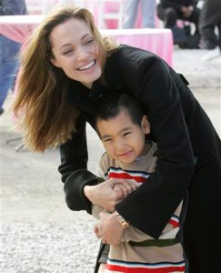 "FILE - In this Dec. 3, 2007, file photo, actress Angelina Jolie talks to her son Maddox, her adopted child from Cambodia, in New Orleans' Lower 9th Ward. Angelina Jolie Pitt adopted Maddox in 2002, and a year later opened a foundation in his name in Cambodia's northwestern Battambang province, which helps fund health care, education and conservation projects in rural Cambodia. She first came to Cambodia 16 years ago to film ""Lara Croft: Tomb Raider."" She's back now for another movie, ""First They Killed My Father,"" as a director, and the subject matter is a far cry from Lara Croft.  (AP Photo/Bill Haber, File)"