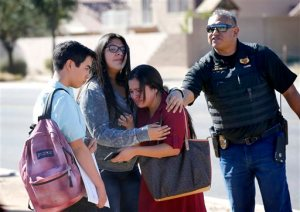 Students embrace after leaving campus, Friday, Feb. 12, 2016, in Glendale, Ariz. after two teens were shot Friday at Independence High School in the Phoenix suburb.   Two 15-year-old girls were shot once at the school, but it was not clear what led up to their deaths, Glendale Officer Tracey Breeden told reporters. Authorities were not looking for anyone else, and a gun was found near the bodies, she said. (AP Photo/Matt York)