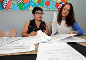 Ana Granado, left, and her daughter Andreia Walker, right, look over healthcare paperwork at their home in Charlotte, N.C., Wednesday, Feb. 10, 2016. Granado had health insurance through the federal health care law and was undergoing treatment for breast cancer when she found out her premiums were going up more than six-fold. She's among hundreds of thousands of people whose coverage is jeopardized annually by paperwork problems. Hundreds of thousands of people lose subsidies under the health law, or even their policies, when they get tangled in a web of paperwork problems involving income, citizenship and taxes. (AP Photo/Chuck Burton)
