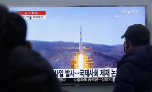 """South Koreans watch a TV news program with a file footage about North Korea's rocket launch plans, at Seoul Railway Station in Seoul, South Korea, Wednesday, Feb. 3, 2016. South Korea warned on Wednesday of """"searing"""" consequences if North Korea doesn't abandon plans to launch a long-range rocket that critics call a banned test of ballistic missile technology. The headline on the screen reads """"North Korea plans to launch a missile."""" (AP Photo/Ahn Young-joon)"""