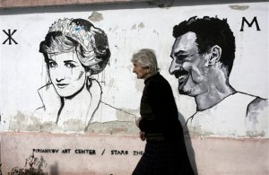 Sabka, 82, passes in front of a mural depicting portrait of Diana Princess of Wales, in the Bulgarian village of Staro Zhelezare on Wednesday, Jan. 27, 2016. The sleepy village of Staro Zhelezare  in central Bulgaria is harnessing the power of celebrities, hoping for an economic revival through art.  Outdoor murals in the village feature local people alongside celebrities on their homes. Homeowners are depicted with personalities such as Pope Francis, Queen Elizabeth II, Angela Merkel, Indira Gandhi, Margaret Thatcher, Barack Obama and Fidel Castro. (AP Photo/Valentina Petrova)