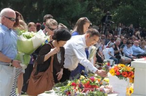 Parents, center, of a Japanese victim in an earthquake, offer flowers during a memorial ceremony in Christchurch, New Zealand Monday, Feb. 22, 2016. Hundreds of people in Christchurch gathered Monday to commemorate the fifth anniversary of an earthquake which killed 185 people. (Kyodo News via AP) JAPAN OUT, MANDATORY CREDIT
