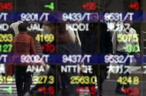 Pedestrians are reflected on an electronic stock at a securities firm in Tokyo Wednesday, March 16, 2016. Asian markets were mixed Wednesday as investors watched for news from a U.S. Federal Reserve policy meeting and from China's annual legislative session. (AP Photo/Eugene Hoshiko)