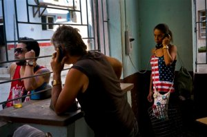 A woman, wearing a cami top with a Stars and Stripes motif, talks by phone at a coffee shop, in Havana, Cuba, Tuesday, March 15, 2016. Five days ahead of the first presidential trip to Havana in nearly 90 years, the U.S. eliminated a ban on Cuban access to the international banking system. The inability to send or receive payments that passed even momentarily through the U.S. banking system had crippled the country's ability to trade with third countries and became a major hindrance to the U.S. attempt to normalize relations with Cuba.  (AP Photo/Ramon Espinosa)