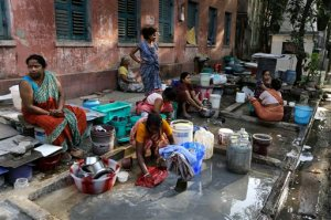 Residents of an area gather around a roadside water source to wash their clothes and fill drinking water for their houses in Kolkata, India, Tuesday, March 22, 2016. A report says India has the world's highest number of people without access to clean water. The international charity Water Aid says 75.8 million Indians or 5 percent of the country's 1.25 billion population are forced to either buy water at high rates or use supplies that are contaminated with sewage or chemicals. (AP Photo/Bikas Das)