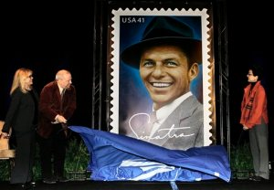 FILE - In this Wednesday, Dec. 12, 2007 file photo, Frank Sinatra's children, from left, Nancy Sinatra, Frank Jr., and Tina, unveil a 10-ft. image of the Frank Sinatra commemorative postal stamp that will be issued by the United States Postal Service, during a ceremony commemorating Sinatra's 92nd birthday, in Beverly Hills, Calif. Frank Sinatra Jr., who carried on his famous father's legacy with his own music career, died unexpectedly of cardiac arrest while on tour Wednesday, March 16, 2016, his family said. He was 72. (AP Photo) (AP Photo/Damian Dovarganes)