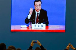 Journalists use their cell phone to record a big screen showing Chinese Premier Li Keqiang during a press conference after the closing session of the annual National People's Congress held in Beijing's Great Hall of the People on Wednesday, March 16, 2016. (AP Photo/Ng Han Guan)