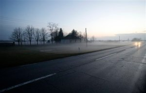 A car travels on the road near the Serbian border with Hungary during foggy twilight in the village of Hajdukovo, Serbia, Tuesday, Feb. 23, 2016. Human trafficking is back in a big way in the Serbian capital and elsewhere along the Balkan migrant corridor _ a veritable growth industry for locals as European Union nations slam their borders shut in a domino effect, leaving thousands of refugees stuck at Greece's northern border. (AP Photo/Darko Vojinovic)