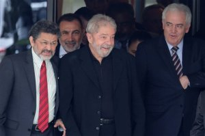 Brazil's former President Luiz Inacio Lula da Silva, center, smiles as he leaves a breakfast with senators of the government's allied base, in Brasilia, Brazil, Wednesday, March 9, 2016. (AP Photo/Eraldo Peres)
