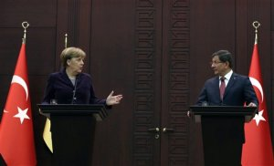 """German Chancellor Angela Merkel, left, speaks to the media during a joint news conference with Turkish Prime Minister Ahmet Davutoglu in Ankara, Turkey, Monday, Feb. 8, 2016. Turkey and Germany agreed on Monday on a set of measures to deal with the Syrian refugee crisis, including a joint diplomatic initiative aiming to halt attacks against Syria's largest city. Merkel said after talks with Davutoglu that she is """"not just appalled but horrified"""" by the suffering caused by Russian bombing in Syria. (AP Photo/Burhan Ozbilici)"""