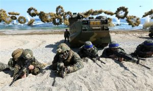 FILE - In this March 12, 2016 file photo, U.S. Marines, left, and South Korean Marines, wearing blue headbands on their helmets, take positions after landing on the beach during the joint military combined amphibious exercise, called Ssangyong, part of the Key Resolve and Foal Eagle military exercises, in Pohang, South Korea. It's a demand North Korea has been making for decades: The U.S. and South Korea must immediately suspend their annual military exercises if they want peace on the Korean Peninsula. And, once again, it's a demand that is falling on deaf ears. This year's exercises are bigger than ever before and reportedly include training to take out Kim Jong Un himself. For Pyongyang's ruling regime, that's a bridge too far. But probably not far enough to fire the first shots over. (Kim Jun-bum/Yonhap via AP, File) KOREA OUT