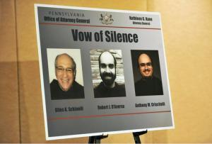 This photo from March 15, 2016, shows a poster from the Pennsylvania State Attorney General with the images of three ex-leaders of the Franciscan religious order at a news conference where Attorney General Kathleen Kane announced criminal conspiracy charges against them in Johnstown, Pa. Robert D'Aversa, Anthony Criscitelli, and Giles Schinelli, are scheduled to surrender Friday, March 18 said Jeffrey Johnson, a spokesman for the Pennsylvania attorney general's office. They're charged with child endangerment and criminal conspiracy. (Todd Berkey/The Tribune Democrat via AP)