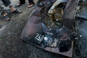 Palestinians inspect abandoned parts with the registration plate of an Israeli army vehicle that was burned during an Israeli army raid in the West Bank refugee camp of Qalandia, at the outskirts of Ramallah, Tuesday, March 1, 2016. Israeli troops raided a Palestinian refugee camp north of Jerusalem early Tuesday to rescue a pair of soldiers who had lost their way and came under attack in the area, the military said. Palestinian health officials said 22 year-old Palestinian Eyad Sajadiyeh was killed and four others were wounded in the ensuing clashes. (AP Photo/Nasser Nasser)