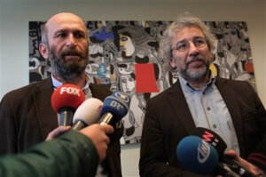 Can Dundar, the editor-in-chief of opposition newspaper Cumhuriyet, right, and Erdem Gul, the paper's Ankara representative speak to the media at the headquarters of Cumhuriyet in Istanbul, after hours their release on Friday, Feb. 26, 2016. Two journalists imprisoned for their reports on alleged government arms-smuggling to Syria were released from jail early on Friday hours after Turkey's highest court ruled that their rights were violated. The two were jailed in November, months after the center-left opposition daily Cumhuriyet published what it said were images of Turkish trucks carrying ammunition to Syrian militants.  (AP Photo/Can Erok)