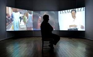 Fashion designer Isaac Mizrahi is silhouetted against a biographical film montage, included in a solo exhibition of his works at the Jewish Museum, Monday, March 14, 2016, in New York. (AP Photo/Bebeto Matthews)