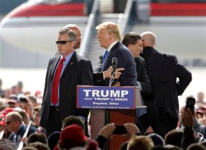 Security personnel surround Republican presidential candidate Donald Trump after a man tried to rush the stage during a rally in Vandalia, Ohio, outside of Dayton, on Saturday, March 12, 2016. The man was stopped and Trump continued with his speech. (Lisa Powell/The Dayton Daily News via AP)  LOCAL PRINT OUT; LOCAL TELEVISION OUT; WKEF-TV OUT; WRGT-TV OUT; WDTN-TV OUT; MANDATORY CREDIT