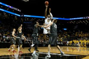 Virginia Commonwealth forward Mo Alie-Cox (12) goes to the basket against Davidson forward Peyton Aldridge and forward Nathan Ekwu (1) during the first half of an NCAA college basketball game during the semifinals of the Atlantic 10 men's tournament, Saturday, March 12, 2016, in New York. (AP Photo/Mary Altaffer)