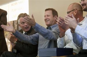 Gary Fish, founder of Deschutes Brewery holds his hands out to an applauding crowd with Gov. Terry McAuliffe, left and Deschutes Brewery representatives, right during the announcement for plans to build a production brewery Tuesday, March 22, 2016 in Roanoke, Va. Virginia will become home to Deschutes Brewery's East Coast operations after beating out North and South Carolina for the coveted facility that's expected to create more than 100 new jobs, Gov. Terry McAuliffe said Tuesday. (Heather Rousseau/The Roanoke Times via AP) LOCAL TELEVISION OUT; SALEM TIMES REGISTER OUT; FINCASTLE HERALD OUT;  CHRISTIANBURG NEWS MESSENGER OUT; RADFORD NEWS JOURNAL OUT; ROANOKE STAR SENTINEL OUT; MANDATORY CREDIT