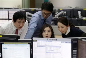 Currency traders work at the foreign exchange dealing room of the KEB Hana Bank headquarters in Seoul, South Korea, Thursday, March 17, 2016. Most Asian stocks rose Thursday, tracking gains on Wall Street after the Federal Reserve left interest rates unchanged and forecast it will raise rates more gradually than it had envisioned last year. (AP Photo/Ahn Young-joon)