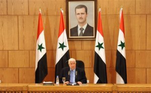 In this photo released by the Syrian official news agency SANA, Syrian Foreign Minister Walid al-Moallem sits beneath a portrait of Syrian President Bashar Assad as he speaks during a press conference in Damascus, Syria, Saturday, March 12, 2016. The Syrian government will send a delegation to Geneva to take part in U.N.-sponsored indirect peace talks with the opposition but has rejected the U.N. envoy's call for presidential elections to be held in the next 18 months. (SANA via AP)