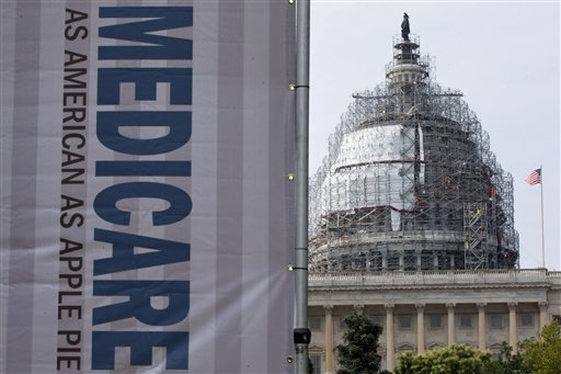 FILE - In this July 30, 2015 file photo, a sign supporting Medicare is seen on Capitol Hill in Washington as registered nurses and other community leaders celebrate the 50th anniversary of Medicare and Medicaid. Medicare. From Akron to Tampa Bay, from New York City to San Francisco, Medicare on Friday, April 1, 2016, launches an ambitious experiment changing how it pays for hip and knee replacements to raise quality and lower costs.  (AP Photo/Jacquelyn Martin, File)