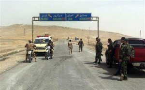 In this photo released by the Syrian official news agency SANA, Syrian government soldiers gather at the entrance of the town of Palmyra, central Syria, Thursday, March 24, 2016. Syrian government forces pushed into the ancient town of Palmyra, where Islamic State militants appeared on the verge of collapse Thursday, while in Iraq, a military spokesman announced the start of a long-awaited operation to recapture the IS-held northern city of Mosul. (SANA via AP)
