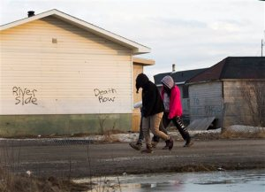 Teenage girls walk through the streets in the northern Ontario First Nations reserve in Attawapiskat, Ontario, Canada, on Monday, April 18, 2016. Natan Obed, president of Inuit Tapiriit Kanatami, the leader of the country's national Inuit organization says his people are dealing with devastating rates of suicide. Obed said he hopes the government will move forward on a plan designed specifically to help Inuit people. (Nathan Denette/The Canadian Press via AP) MANDATORY CREDIT