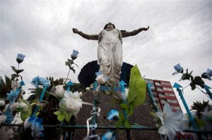 In this April 1, 2016 photo, artificial flowers adorn the base of a statue of Yemanja, the African goddess of the seas, along a promenade in Montevideo, Uruguay. The Catholic Church recently proposed erecting a statue of the Virgin Mary in a park next to a popular promenade, a debate erupted over whether religious symbols in public places violate the separation between church and state. Supporters of erecting the Virgin Mary statue in a public place note that the Uruguayan capital has a statue for Yemanja. (AP Photo/Matilde Campodonico)