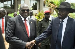 South Sudan's First Vice President Riek Machar, left, and President Salva Kiir, right, shake hands following the first meeting of a new transitional coalition government, in the capital Juba, South Sudan Friday, April 29, 2016. The two leaders have formed a transitional coalition government including politicians from the government and the armed opposition who have been at war for the last two and a half years. (AP Photo/Jason Patinkin)