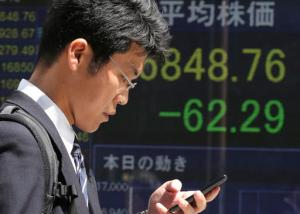 A man walks by an electronic stock board of a securities firm in Tokyo, Friday, April 15, 2016. Asian stocks mostly edged lower on Friday as investors assessed a report on Chinese quarterly economic growth while Japanese shares dropped after an earthquake. Market players were also watching for cues on currencies and other policies from a meeting in Washington, D.C., of financial ministers and central bank governors of the Group of 20 leading industrial nations. (AP Photo/Koji Sasahara)