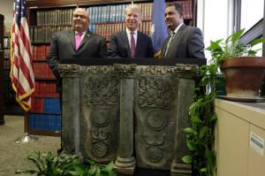 Homeland Security Investigations New York Special Agent in Charge Angel Melendez, left, Manhattan District Attorney Cyrus Vance Jr.,, center, and Pakistan's U.S. Deputy Chief of Mission Rizwan Saeed Sheikh, pose an ancient Buddhist sculpture during a news conference in Vance's offices, in New York, Wednesday, April 27, 2016. Prosecutors returned the sculpture to the government of Pakistan after a Japanese antiquities dealer pleaded guilty to smuggling it into the U.S. The 70-year-old art dealer said he was motivated partly by a desire to protect Buddhist art from being neglected or destroyed in Pakistan. (AP Photo/Richard Drew)